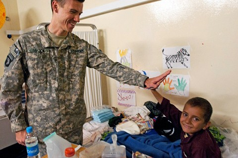 U.S. Army Maj. (Dr.) Patrick Smock, an orthopedic surgeon from Liberty Hill, Texas, 745th Forward Surgical Team, gives a high-five to Abas, a 9-year-old Afghan boy, Nov. 30th at the 426th Brigade Support Battalion Aid Station on Forward Operating Base Fenty. (Photo by U.S. Army Staff Sgt. Ryan C. Matson, Task Force Bastogne Public Affairs)