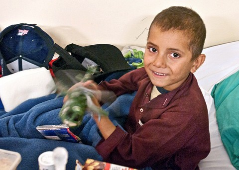Abas, a 9-year-old Afghan boy from the village of Kakrat, plays with a toy helicopter Nov. 30th in his bed at the Aid Station on Forward Operating Base Fenty. The medics of the 426th Brigade Support Battalion, 1st Brigade Combat Team, 101st Airborne Division, have been treating Abas for severe burns to both legs since the unit's arrival to Afghanistan eight months ago. (Photo by U.S. Army Staff Sgt. Ryan C. Matson, Task Force Bastogne Public Affairs)