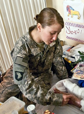 U.S. Army Pfc. Deana Hilburn feels the feet of Abas, a 9-year-old Afghan boy who is being treated for severe burns to both legs, to see if he can feel it Nov. 30th at the Aid Station on Forward Operating Base Fenty. (Photo by U.S. Army Staff Sgt. Ryan C. Matson, Task Force Bastogne Public Affairs)