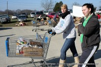 A woman walks back to her car as a volunteer pushes her cart of food.