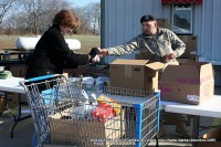 A Fort Campbell soldier hands an item to another volunteer filling a cart for the needy.