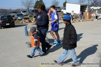 A woman and her two children walk back to their car after picking up a basket of food.