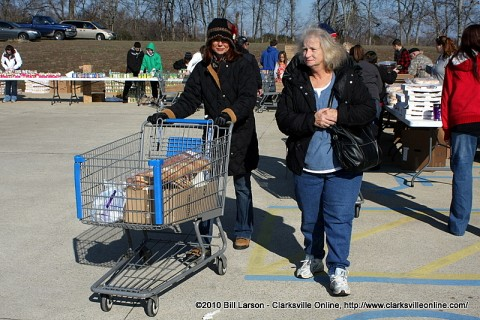 A volunteer pushes a cart full of groceries to the car for an elderly woman.