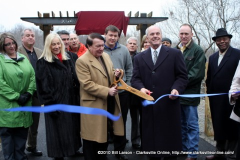 Members of the Hand Family and City officials cut the ribbon opening the Raymond C. Hand Pass pedestrian bridge on the Clarksville Greenway