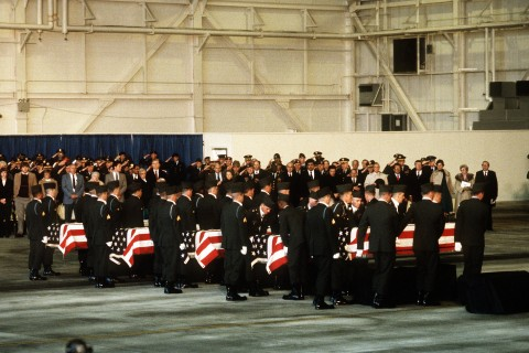 Mourners looks on as members of the 101st Airborne Division carry a casket containing the remains of members of the 3rd Bn., 502nd Inf., 101st Airborne Div., into a hangar for a memorial service. On December 12, 1985, 248 soldiers of the 3rd Battalion were killed in a plane crash at the Gander Airport, Newfoundland, Canada. They were returning to the United States after participating in peacekeeping duty with the Multi-national Force and Observers in the Sinai Desert.