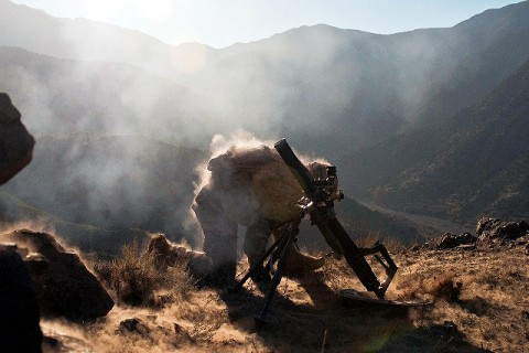 U.S. Army Spc. Corey C. Canterbury, a mortarman from Ocean Springs, MS, assigned to Company B, 2nd Battalion, 327th Infantry Regiment, Task Force No Slack, 1st Brigade Combat Team, 101st Airborne Division, kneels down after firing a mortar round on a mountainside overlooking the Ganjgal Valley in eastern Afghanistan Dec. 11th. (Photo by U.S. Army Staff Sgt. Mark Burrell, Task Force Bastogne Public Affairs)