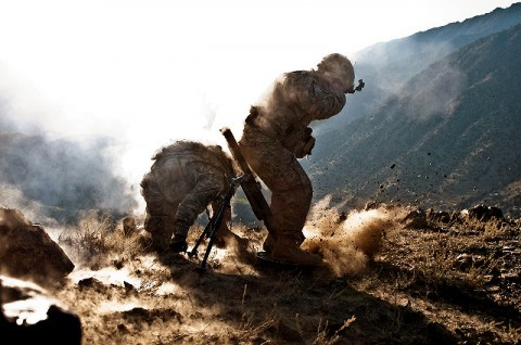 U.S. Army Sgt. Richard A. Darvial (kneeling), a combat medic from Amery, WI, takes cover while U.S. Army Spc. Corey C. Canterbury, a mortar man from Ocean Springs, MS, fires mortars from a mountain top overlooking the Ganjgal Valley in eastern Afghanistan's Kunar Province Dec. 11th. (Photo by U.S. Army Staff Sgt. Mark Burrell, Task Force Bastogne Public Affairs)