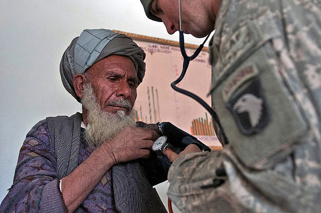 Gul Alam (left), an Afghan metalworker, gets checked out by U.S. Army Sgt. Robert A. Serrano, a combat medic from Staten Island, NY, Task Force Panther, during a free clinic in the Mannakhil Comprehensive Health Care Center in Sherzad District in eastern Afghanistan's Nangarhar Province Dec. 26th. (Photo by U.S. Army Staff Sgt. Mark Burrell, Task Force Bastogne Public Affairs)