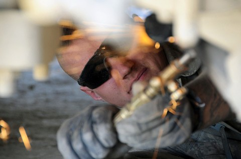 U.S. Army Spc. Eric Lindemann, mechanic from Company E, 1st Battalion of the 506th Infantry Regiment, 4th Brigade Combat Team, 101st Airborne Division and native of Flint, MI, uses a cutting torch to remove a fused bolt from a vehicle's undercarriage on Forward Operating Base Waza Khaw Nov. 20th. (Photo by U.S. Army Spc. Kimberly K. Menzies, Task Force Currahee Public Affairs)