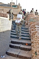 U.S. Army Pfc. Zach Hanood, a mortarman with Company A, 1st Battalion, 133rd Infantry Regiment, from Reinbeck, Iowa, carries a stack of holiday mail packages down the stairs at Combat Outpost Najil Dec. 24th. (Photo by U.S. Army Staff Sgt. Ryan C. Matson, Task Force Red Bulls Public Affairs)