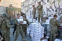Soldiers from Company A, 1st Battalion, 133rd Infantry Regiment stack boxes of holiday mail and care packages to divide out amongst the company Dec. 24th at Combat Outpost Najil. (Photo by U.S. Army Staff Sgt. Ryan C. Matson, Task Force Red Bulls Public Affairs)
