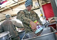 U.S. Army Spc. Lee Goddard, Company E, 1st Battalion, 133rd Infantry Regiment, a truck driver from Dysard, Iowa, helps prepare Christmas dinner for the Soldiers of Company A, 1st Battalion, 133rd Infantry Regiment Dec. 25th at Combat Outpost Najil. (Photo by U.S. Army Staff Sgt. Ryan C. Matson, Task Force Red Bulls Public Affairs)