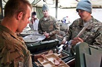 U.S. Army Spc. Lee Goddard, Company E, 1st Battalion, 133rd Infantry Regiment, left, a truck driver from Dysart, Iowa, serves ham to U.S. Army Sgt. Joshua Anderegg, an infantryman from Garber, Iowa, with Co. A, 1st Bn., 133rd Inf. Regt., Dec. 25th at Combat Outpost Najil. (Photo by U.S. Army Staff Sgt. Ryan C. Matson, Task Force Red Bulls Public Affairs)