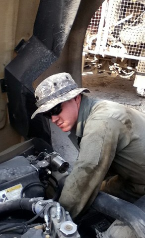 U.S. Army Spc. Thomas Floyd, wheeled vehicle mechanic, 2nd Battalion, 320th Field Artillery Regiment, repairs an armored vehicle in his motor pool on Forward Operating Base Hughie Dec. 20th. Floyd, a Colton, OR, native, is on his second deployment to Southwest Asia. (Photo by U.S. Army Spc. Tommy Porter, 2nd Battalion, 320th Field Artillery Regiment)