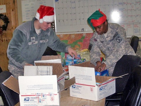 U.S. Army Pfc. Cody Smith, an intelligence analyst from York, PA, and U.S. Army Staff Sgt. Randie Lewis, a senior intelligence analyst from Watertown, NY, both with Headquarters Support Company, Task Force Mountain Eagle, 10th Combat Aviation Brigade, 10th Mountain Division, pack care packages at Bagram Airfield for Soldiers in remote areas of Regional Command–East Dec. 18th. (Photo by U.S. Army Sgt. George Tucker, TF Mountain Eagle)