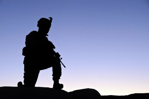 A Soldier from Headquarters and Headquarters Company, 1st Battalion, 506th Infantry Regiment, 4th Brigade Combat Team, 101st Airborne Division kneels in an over-watch position on top of a qualot wall during their last deployment. (Photo by Spc. Luther L. Boothe Jr., Task Force Currahee Public Affairs Office)