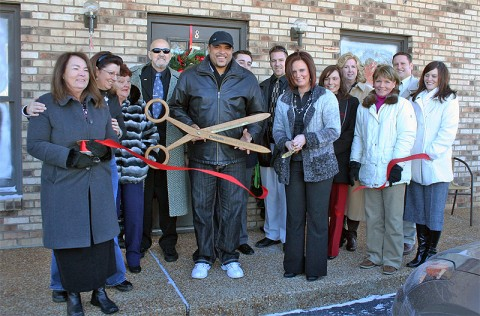 Claudia George, owner of Shear Madness, cuts the ribbon to officially open her new business, located at 2150 Wilma Rudolph Blvd. Suite 8, while members of the Clarksville Chamber of Commerce look on.
