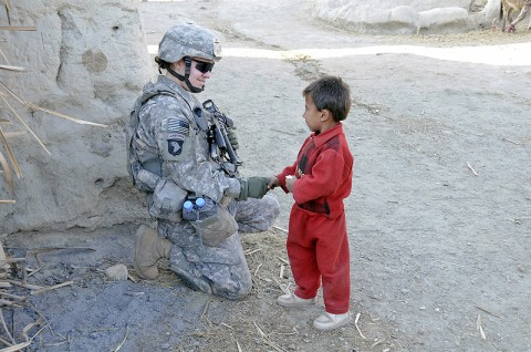 U.S. Army Spc. Lauren Hyman of Texarkana, Texas, armored vehicle driver for the 64th Military Police Company based at Combat Oupost Fortress, says hello to an Afghan child during a foot patrol in Noor Gal District Jan. 3rd. Hyman and U.S. Army Spc. Cristine Gallagher of Victorville, CA, are the only two females assigned to COP Fortress. (U.S. Army photo by U.S. Air Force Capt. Peter Shinn/RELEASED)