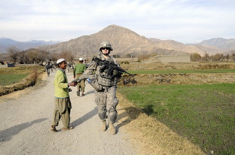 U.S. Army Spc. Lauren Hyman of Texarkana, Texas, an armored vehicle driver for the 64th Military Police Company based at Combat Oupost Fortress, greets an Afghan child during a foot patrol in Noor Gal District Jan. 3rd. (Photo by U.S. Air Force Capt. Peter Shinn/RELEASED)