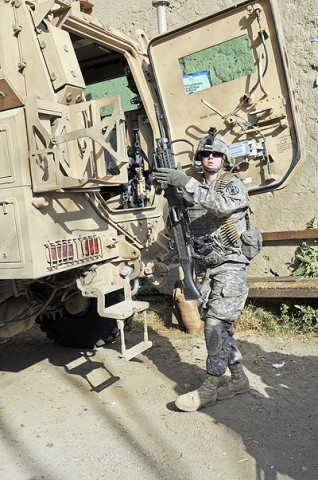 U.S. Army Spc. Cristine Gallagher of Victorville, CA, machine-launched grenade gunner for the 64th Military Police Company based at Combat Outpost Fortress, prepares her weapon for a foot patrol through the Noor Gal District Jan. 3rd. (Photo by U.S. Air Force Capt. Peter Shinn/RELEASED)
