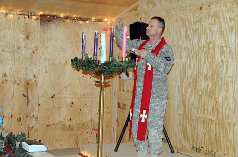 U.S. Army Chaplain (Maj.) Randal H. Robison of Grand Prairie, Texas, brigade chaplain for 4th Brigade Combat Team, 101st Airborne Division, lights the Advent candles during a Catholic mass at the Frontline Chapel at Forward Operating Base Sharana Dec. 24th. (Photo by U.S. Army Sgt. Luther L. Boothe Jr., Task Force Currahee Public Affairs)
