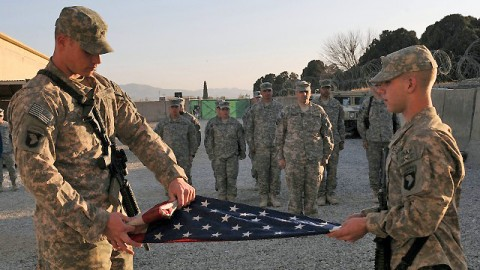 U.S. Army Spc. Nathan Smith of Anchorage, Alaska, and Spc. Barrett McClung of Phoenix, AZ, both from the 404th Civil Affairs Battalion, fold the World Trade Center flag at Forward Operating Base Salerno Jan. 24th. (U.S. Army photo by Spc. Tobey White, Task Force Duke Public Affairs)