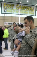 A soldier feeds his new baby for what is likely the first time.