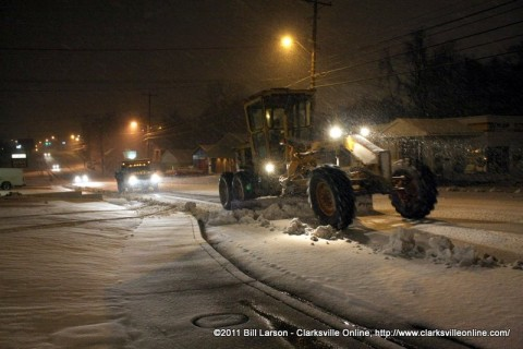 The Clarksville Street Department using graders as snow plows to help clear the still falling snow from city streets