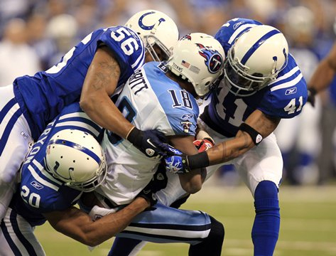 Tennessee Titans wide receiver Kenny Britt, center, is tackled by Indianapolis Colts defenders Tyjuan Hagler (56), Justin Tryon (20) and Antoine Bethea in the first quarter of an NFL football game in Indianapolis, Sunday, Jan. 2nd, 2011. (AP Photo/Michael Conroy)