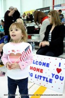 A young girl waits for her daddy SSG Little to enter the hanger