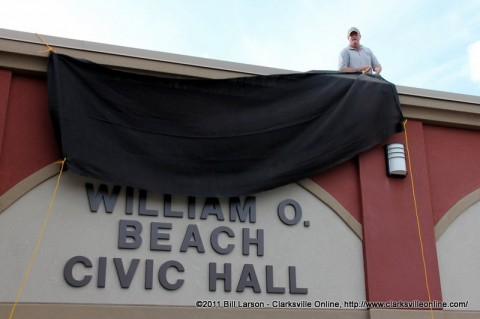 A county worker unveils the name of the re-dedicated Civic Hall