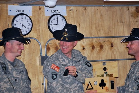 """U.S. Army Lt. Col. Will Johnson, commander of Task Force Panther, 4th Brigade Combat Team, 101st Airborne Division, receives """"panther cologne"""" from Task Force Shooter pilots Capt. Scott Wohlford of Watertown, NY, and Chief Warrant Officer 2 Mark Smith of New Orleans. (Photo by Army Chief Warrant Officer 2 Dave Ratcliffe, Task Force Shooter, 10th Combat Aviation Brigade, TF Falcon)"""