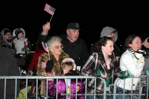 Army Wives and family members cheering for their soldiers who are returning home.