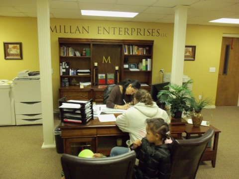 Jil Simpson signing her new lease in the offices of Milan Enterprises