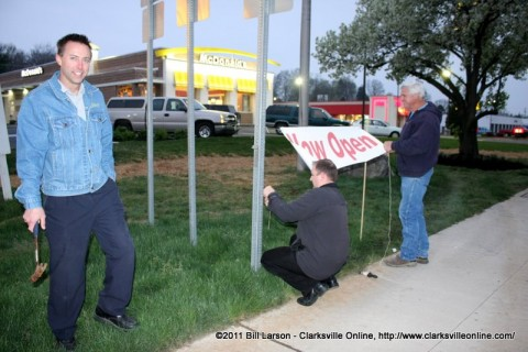 Larson Enterprises owner Eric Larson stands in front of his business as an open sign is hung out by the street