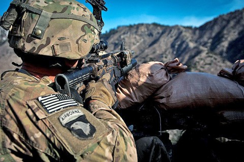 From behind his makeshift fighting position, U.S. Army Sgt. Nathaniel S. Gray, an infantry squad leader from Tupelo, MS, 101st Airborne Division, uses his combat optics to search for insurgent fighters during a recent combat operation in Shigal District of eastern Afghanistan's Kunar Province March 16th. Gray is a single parent with twin sons at home. (Photo by U.S. Army Sgt. 1st Class Mark Burrell, Task Force Bastogne Public Affairs)