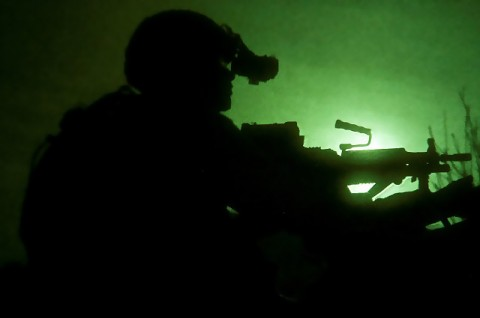 Through a night-vision lens, Task Force No Slack, is silhouetted by the moon while pulling security shortly after being air assaulted to a mountaintop in Shigal Valley in eastern Afghanistan March 16. Multiple companies of Soldiers were dropped in to surround the valley marking the beginning of Operation Eagle Talon. (Photo by U.S. Army Sgt. 1st Class Mark Burrell, 210th Mobile Public Affairs Detachment)
