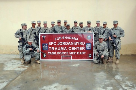 U.S. Army Soldiers from Task Force Red Currahee's 4th Platoon, Company A, 1st Battalion, 506th Infantry Regiment, 4th Brigade Combat Team, 101st Airborne Division, stand with the sign dedicating the new trauma center to a Task Force Currahee medic at Forward Operating Base Sharana March 1st. (Photo by U.S. Army Sgt. Christina Sinders, Task Force Currahee Public Affairs)