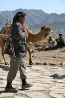 An Afghan Uniformed Police Officer walks past a camel being led by a local farmer in Naka District, Afghanistan during