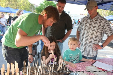 Mission Clarksville  Director and Grower Michael Hampton shows a young festival attendee how to plant her watermelon seed