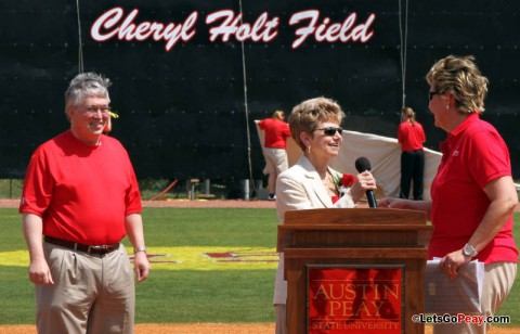 Cheryl Holt takes the microphone from former Lady Govs softball player Susan Cole after the tarp was pulled to dedicate the field to Holt. APSU President Tim Hall, left, also took part in the dedication ceremonies. (Austin Peay Sports Information)