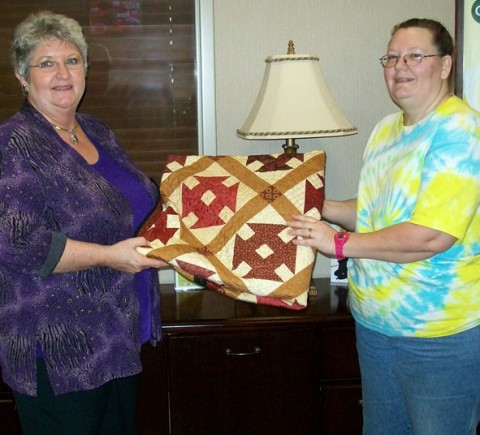 Planters Bank AVP/Branch Manager Jan Greene (L) presents Tammy Durham (R) of Clarksville with the 2011 Patchwork Premiere quilt.