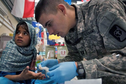 U.S. Army Capt. Adam W. Racusin, an orthopedic surgeon assigned to the 745th Forward Surgical Team, attached to Task Force Bastogne, cleans and bandages Nazawaly Uddin's hand a few weeks after performing surgery on it at Forward Operating Base Fenty, Afghanistan, April 18th. Nazawaly's hand was badly burned by boiling water rendering her hand useless before the surgery. (Photo by U.S. Army Sgt. 1st Class Mark Burrell, Task Force Bastogne Public Affairs)