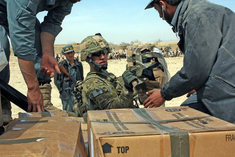 Sgt. Thomas Bohall, a Pathfinder with Task Force Palehorse, helps Afghan National Police load humanitarian relief items onto a truck in the village of Deh Gholaman in Kandahar province, March 18th. The ANP officers distributed the items to the people in the village who are facing a difficult year due to poor crops. (Photo by Sgt. 1st Class Stephanie Carl)