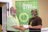 Maurice Vaughn of Better Homes and Garden Real Estate Hometown Connection presents a donation to Kenny York of Mana Café Ministries
