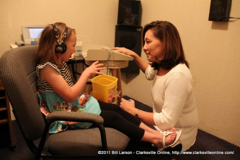 """Dr. Emiko """"Emi"""" LeJeune giving a young girl a hearing test"""