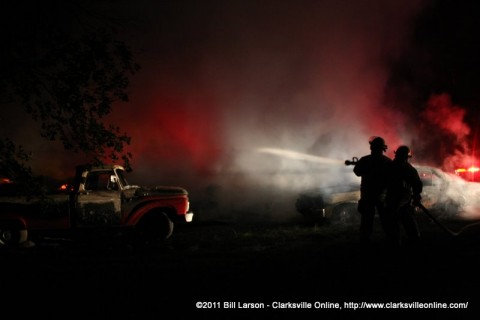 Fire fighters attacking the blade on Webb Road, the two burned out vehicles can be seen