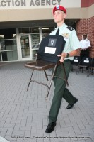 A MCHS JROTC Student solemnly carries one of the chair representing a missing service member