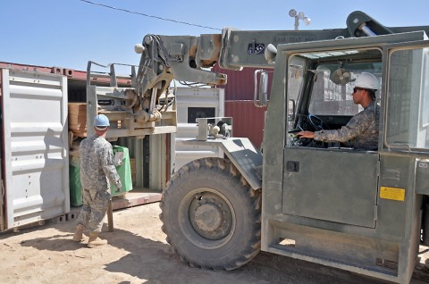 Spc. Jason Morrison of the 101st Sustainment Brigade carefully helps guide Sgt. Justin Scott, a Military Heavy Equipment Opertator with the 919th Inland Cargo Transportation Company, 17th Combat Sustainment Support Battalion, 101st Sustainment Brigade, sheets of plywood inside a conex. The plywood, along with other building material, is used to help Soldiers contruct their own wooden B-Huts in remote Forward Operating Bases throughout Afghanistan. (Photo by Sgt. 1st Class Peter Mayes)