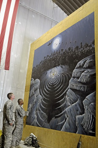 Sgt. 1st Class Narada Johnson and Spc. Blake Chambers, 101st Sustainment Brigade, look on at the 14 foot mural recently completed in the Rigger Shed at Bagram Air Field. (Photo by Spc. Michael Vanpool)